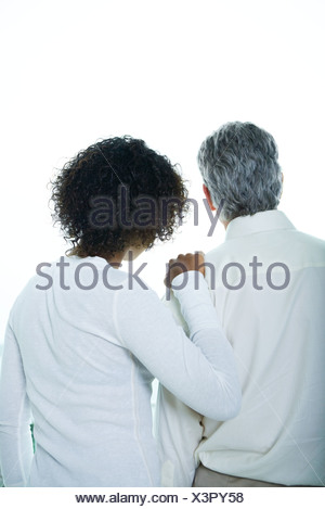 Young woman with hand on mature man's shoulder, rear view, waist up - Stock Photo