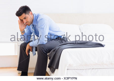 Frowning businessman sitting at edge of bed - Stock Photo