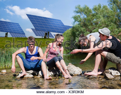 People sitting in river by solar panels - Stock Photo