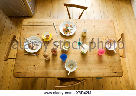 Overhead view of breakfast table with eaten food and messy plates - Stock Photo
