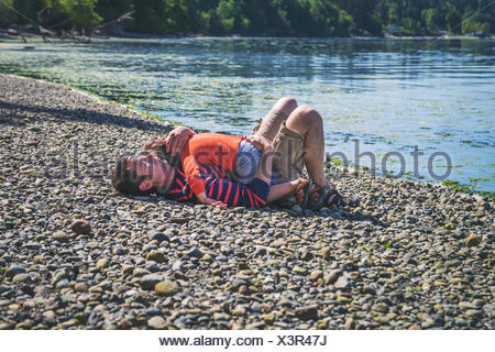 Young boy and father sleeping on the beach - Stock Photo