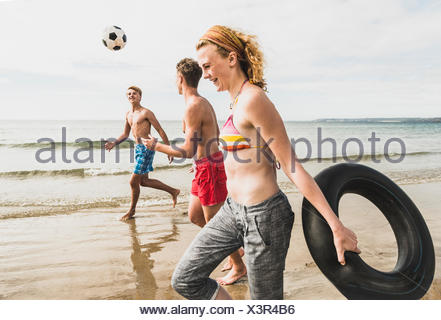 Friends walking with a ball and tyre on the beach - Stock Photo