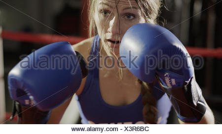 Close up of female boxer in boxing gloves standing in boxing ring during match - Stock Photo