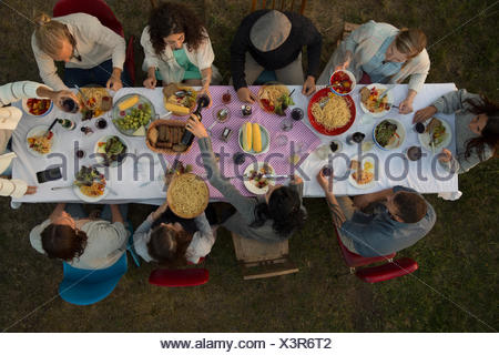 Overhead view friends eating and drinking at garden party dinner - Stock Photo