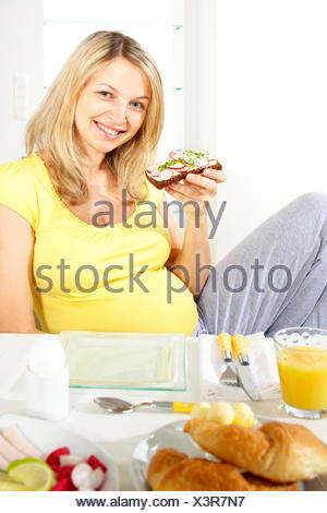 young pregnant woman at the breakfast table - Stock Photo