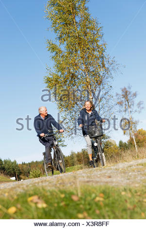Sweden, Sodermanland, Man and woman cycling - Stock Photo