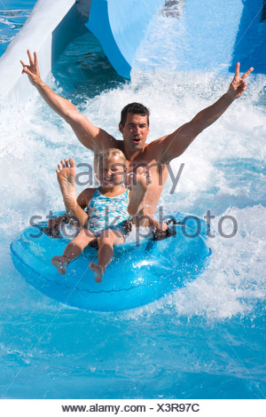 Father and daughter sliding down waterslide on innertube in water park - Stock Photo