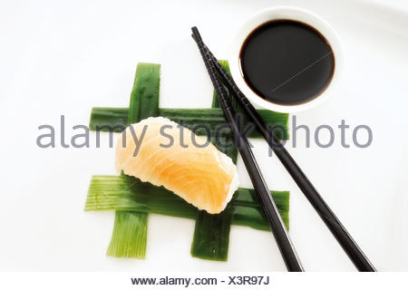 Sushi Nigiri, made with salmon and rice, placed beside black chopsticks and a bowl of soy sauce on interwoven leek strips - Stock Photo