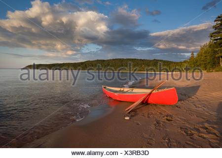 Red canoe on sandy beach of Gargantua Bay in Gargantua Harbour on Lake Superior in Lake Superior Provincial Park Ontario Canada - Stock Photo