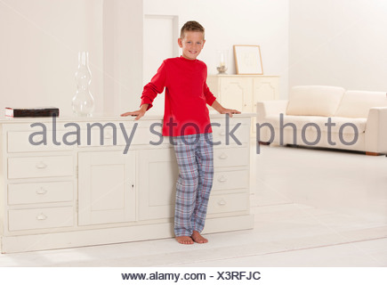 Boy in pajamas leaning on desk - Stock Photo