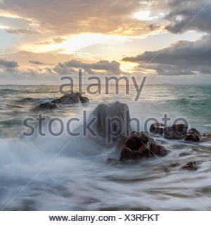 Waves crashing against rocks - Stock Photo