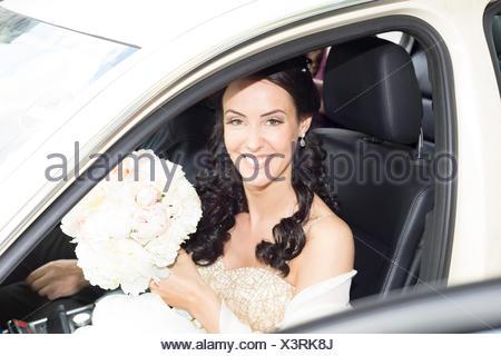 Smiling bride in car - Stock Photo