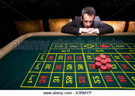 Businessman looking at pile of gambling chips on roulette table - Stock Photo