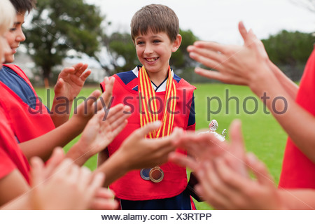 Children cheering teammate with trophy - Stock Photo