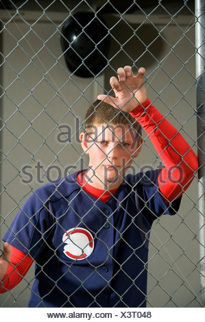 Serious baseball player standing in dugout - Stock Photo
