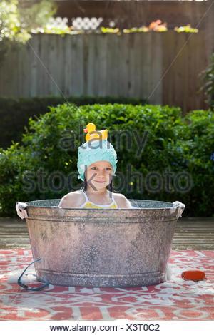 Portrait of girl in bubble bath in garden with rubber duck on head - Stock Photo