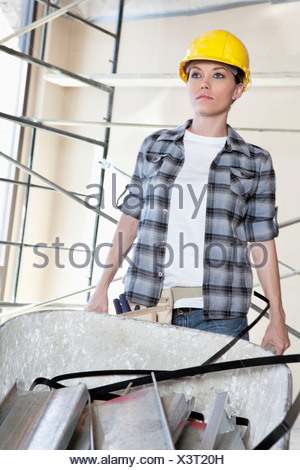 Front view of female worker pushing wheelbarrow at construction site - Stock Photo