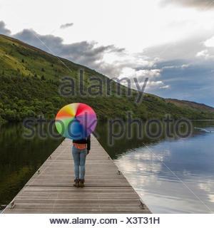 UK, Scotland, Woman with umbrella on jetty - Stock Photo