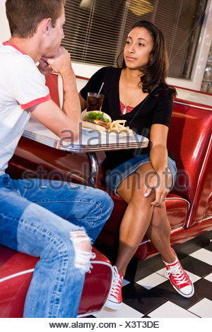 Multiracial teen couple having lunch in diner - Stock Photo