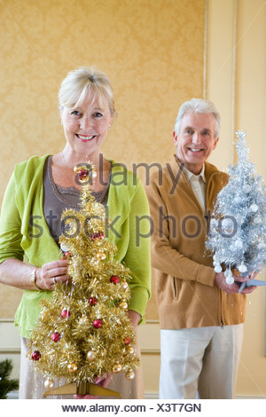 Senior couple with ornamental Christmas trees, smiling, portrait, close-up of woman - Stock Photo