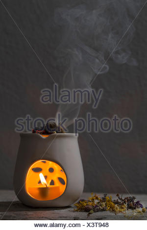 burning incense with herbs, aroma lamp - Stock Photo