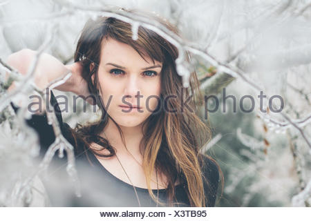 Portrait of young woman standing amongst frozen branches - Stock Photo