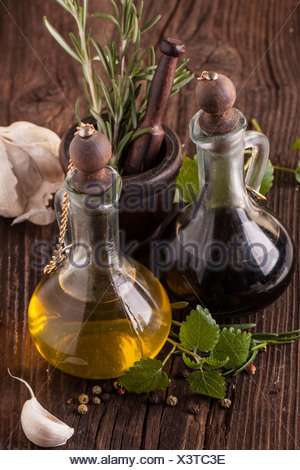 Top view on olive oil and vinegar in vintage bottles on wooden table with garlic, mint and rosemary in wooden mortar - Stock Photo