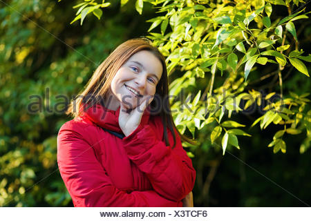 Smiling woman in a red jacket - Stock Photo