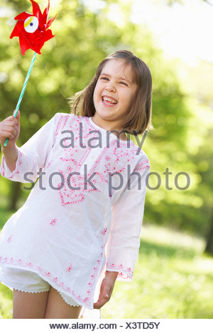 Young Girl Walking Through Summer Field Carrying Windmill - Stock Photo