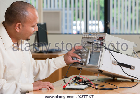 Hispanic engineering student adjusting signal levels on oscilloscope and function generator in a classroom - Stock Photo
