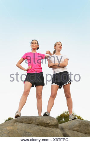 Portrait of two proud female runners on top of rock formation - Stock Photo
