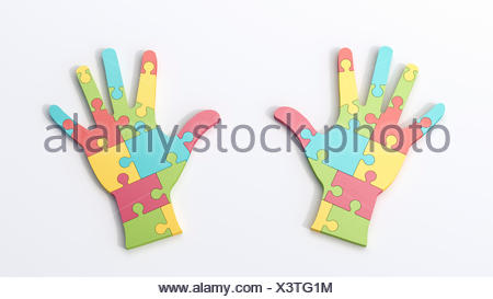 Two multicolored puzzle hands - Stock Photo
