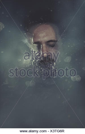 concept suicide, man submerged in blue water - Stock Photo