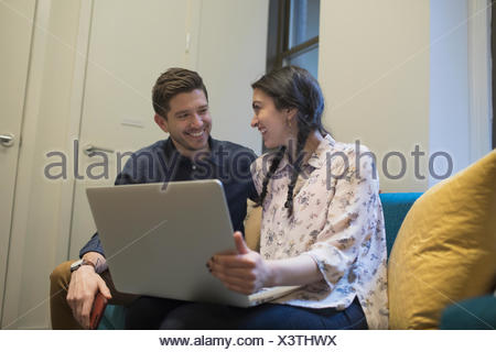 Young professionals working on laptop in an office - Stock Photo