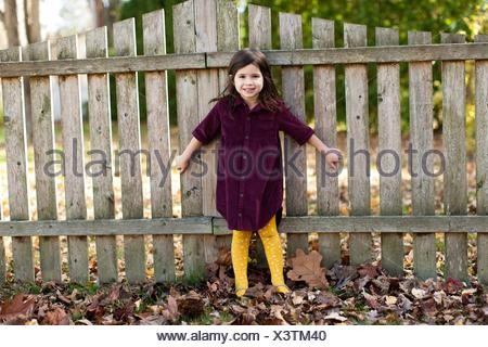 Full length front view of girl standing against garden fence looking at camera smiling - Stock Photo