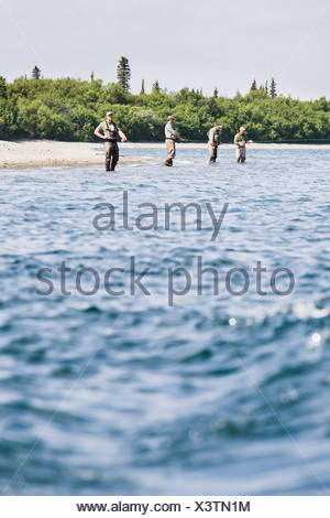 View From The Water Of Four Sport Fishermen In Chest Waders Lined Up Fishing For Bristol Bay Sockeye Salmon In The Kvichak River - Stock Photo
