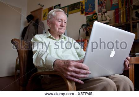 Elderly man, senior citizen holding an Apple Macintosh laptop computer on his knees, nursing home, retirement home, Berlin - Stock Photo