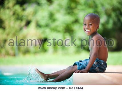 Portrait of boy (4-5) splashing feet in pool, Johannesburg, Gauteng Province, South Africa - Stock Photo