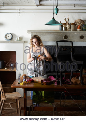 Woman decorating chair with fabric - Stock Photo