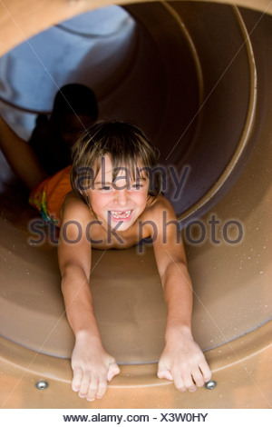 Portrait of a boy sliding in tunnel slide - Stock Photo