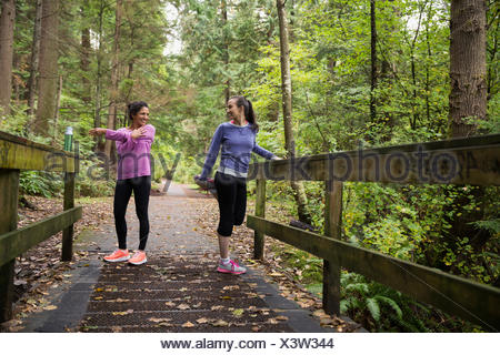 Mother and daughter stretching preparing for run woods - Stock Photo