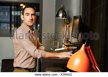 Portrait of businessman at office desk - Stock Photo