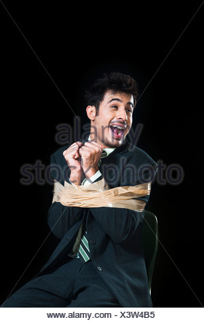 Businessman tied up with adhesive tape and looking frustrated - Stock Photo