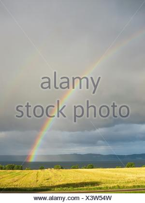 Idyllic View Of Rainbow Over Grassy Field - Stock Photo