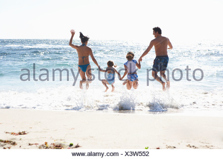Two generation family wearing swimwear jumping above surf on sandy beach side by side holding hands rear view sunlight shimmerin - Stock Photo