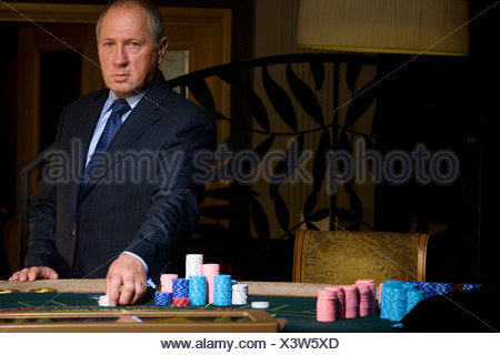 Mature man gambling, hand on chips, portrait - Stock Photo