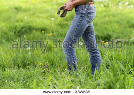 A female walking in grass and wildflowers holding work gloves; Ellston, Iowa, United States of America - Stock Photo