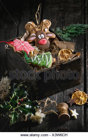 Christmas Handmade patterned gingerbreads as Christmas tree, reindeer Rudolph and snowflake shapes in wooden box over old wooden - Stock Photo