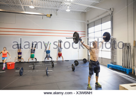 Man lifting barbell in gym - Stock Photo