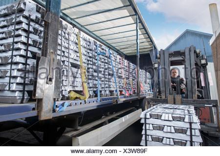 Forklift lifting aluminum ingots onto truck - Stock Photo